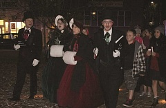 Photo Credit: LINDSAY KEEFER - Dickens carolers bring walkers into the Downtown Plaza while singing carols.