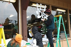 Photo Credit: POST PHOTO: KYLIE WRAY - Dan Kruse, a senior, was in charge of painting the holiday greeting on the Sandys window of Ace Hardware.