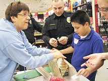 Photo Credit: SUBMITTED - Shopping spree - Shop with a Cop, now in its fourth year, connects low-income children with police officers for a holiday shopping trip at the Newberg Fred Meyer store.