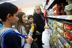 Photo Credit: TIMES PHOTO: JAIME VALDEZ - Fifth-graders Abdullah Alabadi, left, Riley Suzuki and Mukund Sammi consult with Sexton Mountain Elementary Principal Teresa Clemens-Brower on a price of an item at Walmart.