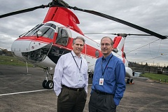 Photo Credit: TRIBUNE PHOTO: JONATHAN HOUSE - New CEO Jim Rankin (left) and Chairman Stan Wilson stand in front of one of the Boeing Vertol helicopters at Columbia Helicopters.