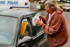 Photo Credit: DAVID F. ASHTON - Retiring City of Portland Office of Neighborhood Involvement Crime Prevention Coordinator Katherine Anderson takes a bag of medications at the drive up Drug Turn-in event