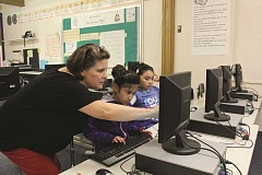Photo Credit: TYLER FRANCKE | WOODBURN INDEPENDENT - Woodburn After School Club Coordinator Karen Armstrong helps second-graders Amy Padilla, center, and Yamiley Cienfuego-Ascencio with a computer science exercise during last week's Hour of Code event at Nellie Muir Elementary School. Woodburn participated in the exercise as part of Computer Science Education Week.