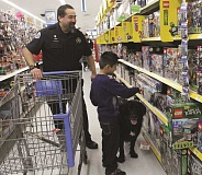 Photo Credit: TYLER FRANCKE | WOODBURN INDEPENDENT - Washington Elementary School second-grader Gael Lily Maldonado peruses the selection of Lego sets at the Walmart in Woodburn Thursday during the store's first-ever 'Shop with a Cop' event, accompanied by Woodburn Police Department K-9 officer Grizz, a narcotics detection dog, and his handler, Det. Tim Cobos.