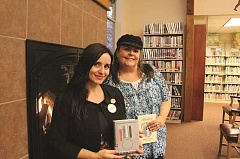 Photo Credit: LINDSAY KEEFER - Mount Angel Public Library Director Carrie Alexandria Caster, left, and children's librarian Theodora Rudolph hold books in front of the library's welcoming fireplace. Both women were recently hired, making up two-thirds of the library staff.