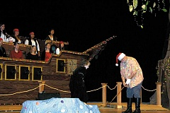 Photo Credit: PEGGY SAVAGE - Santa practices his golf swing, right, as a Molalla High School choir group aboard Captain Hook's pirate ship sings a Christmas carol in the Molalla High School presentation of 'Christmas in Neverland.' The annual Singing Christmas Tree concert drew packed audiences each night of its week-long run.