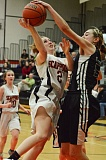 Photo Credit: JOHN WILLIAM HOWARD - Alyssa Spang is blocked at the rim during Mondays loss to Salem Academy. Spang led Scappoose with seven points.