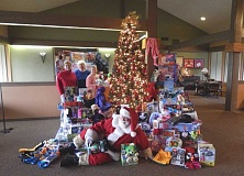 Photo Credit: BARBARA SHERMAN - Santa Claus (aka Don Waddell) is right at home in the Summerfield Clubhouse surrounded by gifts for foster children donated by residents; in the back behind the mountain of presents are Kathy Peper (left), Yvonne Welch and Wynona Neubauer.