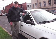 Photo Credit: TYLER FRANCKE | WOODBURN INDEPENDENT - Woodburn resident Rob Smith, 90, pictured here with the Toyota Corolla he drives several times per week in volunteer service to Meals on Wheels in Woodburn. He plans to retire soon for health reasons after more than 20 years serving with the program.