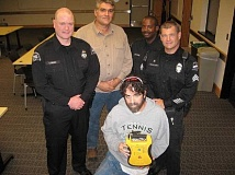 Photo Credit: SHERWOOD GAZETTE: RAY PITZ  - Rob Martin, foreground, holds an AED device similar to the one that saved his life. Those who were there that day to help include, from left, Sgt. Officer Sean Perry, Andre Meyer, Officer Colin Drummond and Sgt. Jon Carlson.