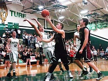 Photo Credit: DAN BROOD - UNDER THE HOOP -- Tualatin High School senior Jacob Bennett looks to put a scoop shot past Tigard freshman Keishon Dawkins during Friday's game.