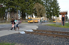 Photo Credit: COURTNEY VAUGHN - Breanna Aaberge and Emily Howard cross railroad tracks near Scappoose High School as they walk home from school. The school district and police recently warned students and parents about legal and safety issues of trespassing the tracks and adjoining easements.
