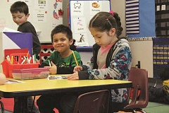 Photo Credit: TYLER FRANCKE | WOODBURN INDEPENDENT - Nellie Muir kindergartners, from left, Ronin Lee Hardiman, Brandon Ortiz Alvarado and Nelly Vitela Chavez, work on a project last week.