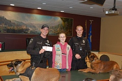 Photo Credit: PHOTO BY: SHAWNDA HORN - Terri-Lee Blue presents a check Friday to officers Dan Shockley and Bill Horton, and their dogs Flint and Mac.