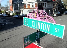 Photo Credit: TRIBUNE PHOTO: KEVIN L. HARDEN - Southeast Clinton Street's neighborhood greenway is celebrated on street signs and bike racks. Increased traffic in the area is putting bike riders and vehicles on a collision course, which worries the city and area residents.