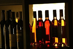 Photo Credit: HILLSBORO TRIBUNE PHOTO: DOUG BURKHARDT - Bottles of wine reflect the glow from a background lamp at Primrose & Tumbleweeds in downtown Hillsboro. The artistic shape of the bottles, combined with the different varieties of wine, provides a colorful display of form and light.