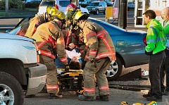 Photo Credit: DAVID F. ASHTON - After extricating the accident victim from the car, paramedics begin to roll the patient on a gurney toward the waiting ambulance.