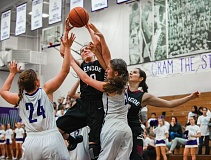 Photo Credit: HILLSBORO TRIBUNE PHOTO: KENT FRASURE - Glencoe sophomore Kaelin Immel gets tangled up with Sunset's Kinley Rowan (5) and Mara Chorro Loeda (24) on a drive to the basket during Tuesday's Metro League basketball game.