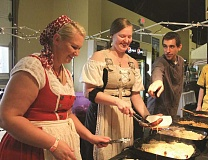 Photo Credit: LINDSAY KEEFER - Glockenspiel Restaurant employees, from left, Anastasia Kuznetsov, Julie Van Valkenburg and Drew Hutchinson dish out sausage at the seventh annual Wurstfest.
