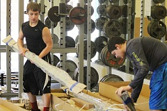 Photo Credit: JEFF WILSON/THE PIONEER - Madras football players Chris North, left, and Kyle Brooks unpack the new weight brackets that will help upgrade the Buffs' weight room.