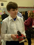 Photo Credit: SPOKESMAN PHOTO: KATE HOOTS - Rory Cheevers, an eighth-grader at Rosemont Ridge Middle School, holds a shoe-based phone charger that utilizes the power of the wearers footsteps.