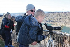 Photo Credit: HOLLY M. GILL - Tim and Alexa Gassner, of Madras, help their sons, Cole, 7, in the foreground, and Jake, 5, look through spotting scopes directed toward eagle nests on Sunday, at the 20th annual Eagle Watch.