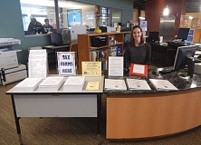 Photo Credit: BARBARA SHERMAN - The IRS used to provide libraries with many forms and instruction books, which filled several shelves at the Tigard Public Library, but due to drastic budget cuts this year, only three basic forms are being provided. Tigard library Adult Services Supervisor Allison Arnold sits by this year's display, which has shrunk to a fraction of its former size.