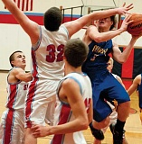 Photo Credit: LON AUSTIN/CENTRAL OREGONIAN - Blake Bartels goes hard to the basket against Seaside's Austin Eagon during Friday's night play-in game at Seaside. The Seagulls won the game 61-52 ending the Cowboys season.