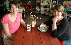 Photo Credit: ESTACADA NEWS PHOTO: ISABEL GAUTSCHI - New owners Dede Brittle (left) and Semira Clark beam in the reopened Mason Jar cafe. Clark shows off a breakfast burrito warmed by a locally made bowl cozy for sale in the vendor section of the business. Brittle and Clark are longtime Estacada residents.