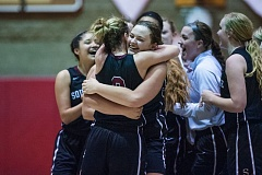 TIMES PHOTO: JOHN LARIVIERE - Southridges Margaret Brock (right) hugs Makenna Bell (left) as the Skyhawks celebrate their 35-31 victory over Oregon City in the second round of the OSAA 6A Girls Basketball Championships on the Pioneers court.