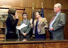 PAMPLIN MEDIA GROUP - Sworn in - New Oregon Secretary of State Jeanne Atkins took the oath of office March 11 from Gov. Kate Brown (back to camera), son John, husband John (holding Bible).