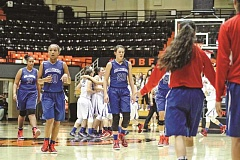 HILLSBORO TRIBUNE PHOTO: - Tarea Green, Maddy Ellsworth and Makenna Gambee (from left) walk off the Gill Coliseum court while La Salle players celebrate their 35-25 Class 5A state quarterfinal victory over Hillsboro last Wednesday. The Falcons went on to win the state title while the Spartans were eliminated last Thursday.