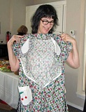SUBMITTED PHOTO - Author Stephanie Lehman sizes up a hand-sewn, vintage dress at the AAUW LO Friendship Tea.