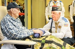 GARY ALLEN - Honored veteran - Local VFW quartermaster Hub Mardock presents an American flag to Wardell Jenkins after a ceremony last week at Marquis Newberg. Jenkins was a soldier who fought the Japanese during the attack on Pearl Harbor in December 1941.