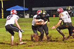 FILE - Mud splashes up from around the feet of football players at Ackerson Stadium, the home field of the St. Helens High School Lions, during a wet-weather game last fall. School officials secured a loan this year to pay for an artificial turf field, after players complained of dangerous conditions on the existing grass field.