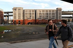 PHOTO CREDIT: TRIBUNE PHOTO: JONATHAN HOUSE - Pedestrians walk by a two-acre property at 2095 S.W. River Parkway, where the city plans to build at least 200 affordable housing unit. The City Council will consider an ordiance to buy one more acre for affordable housing in the area on Wednesday.