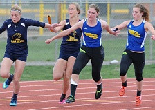 LON AUSTIN/CENTRAL OREGONIAN - Danielle Michael, far right, hands the baton to Audrey Bernard during the final exchange in the 4x100-meter relay. The pair teamed with Madie Bernard and Laken Berlin to win the race with a time of 51.988.