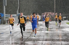 JOHN HOWARD - No fooling. April 1st was a rainy day at St. Helens High School. In the above photo, 4x100-meter relay anchors (left-front) Bryce Bumgardner and (right-front) Parker Cardwell battle one another and the rain. La Salle won the relay, but St. Helens won the boys meet, 80-64. La Salle girls won a barnburner, 71-70.