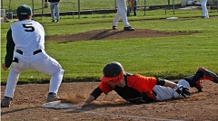 PARKER LEE  - Gladstone senior Ben Fox dives back to first base in last weeks 4-3 win at Estacada. Fox had four stolen bases in the game, and he scored the game-winnimg run.