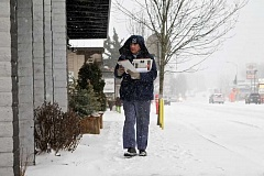 TIMES PHOTO: JAIME VALDEZ - Roger Brosseau, a U.S. postal worker for 26 years, delivers mail in downtown Tigard during snowstorm in February 2014. Last week, the Oregon Legislature urged fedearl authorities to re-classify Tigard's two ZIP codes from 'Portand' to 'Tigard.'