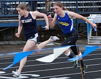 PHOTO COURTESY OF DOUG SMITH - West Albany's Allison Young and Crook County's Audrey Bernard rae to a dead heat in the 4x100 relay. Both teams finished with times of 51.00 in the race. The Cowgirls finished fourth out of eight teams in the meet despite taking just 10 girls to the competition.
