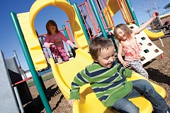 KEVIN SPERL - Lukkas Mullen, 4, jumps off the slide before Cathy Miller, 5, takes her turn, while Nakiya Anderson, 4, watches, during play time at the Head Start playground.