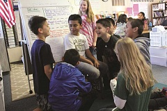 TYLER FRANCKE - A group of Lincoln Elementary School students discuss a reading assignment last week in Sara Chaudhary's fourth-grade class. They are among an estimated 350 students at Lincoln alone who are housed in aging portables that the district hopes to remove and replace if voters approve a $65 million bond proposal May 19. Pictured are, from left, Spencer Karseboom, Jesus Duran, Kaleb Robles and Jose Luis.