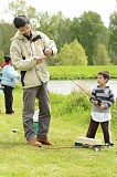 SPOTLIGHT PHOTO: JOHN WILLIAM HOWARD - Charlie Deng (left) baits the line of his son Richard (right) at a family fishing event at Trojan Pond last April.