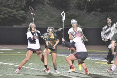 MATTHEW SHERMAN - West Linn's Jessica Weinhart weaves through a trio of Lake Oswego defenders in Tuesday's game with the Lakers. West Linn fell 11-8, its first loss of the season.