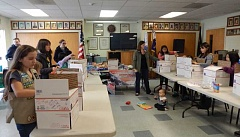 BARBARA SHERMAN - Jennifer Lamaye, with her son Jordan playing on the floor at Tigard American Legion Post 158, instructs Scouts on how to pack boxes of cookies destined for overseas troops.