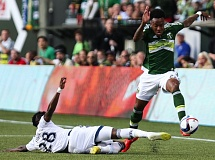 TRIBUNE PHOTO: DAVID BLAIR - Rodney Wallace of the Portland Timbers attempts to hurdle Vancouver Whitecaps tackler Gershon Koffie during Saturday night's 0-0 draw.