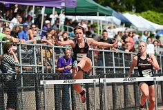 JOHN WILLIAM HOWARD - Scappoose freshman Mackenzie Ela clears the final hurdle in her heat of the 100 meter hurdles at Jesuit High School on Friday, May 1. Ela set a new personal record in the event.