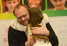 SPOKESMAN PHOTO: VERN UYETAKE - Russell Romas, a language arts and social studies teacher at Rosemont Ridge Middle School, receives a congratulatory hug from his daughter Myrtle.