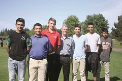 PHIL HAWKINS - The Woodburn boys golf team stands with Charlie Piper (middle), a member of the last Woodburn team to advance to the state championship tournament in 1970. From left: Steven Martinez, Gabriel Hernandez, Julian Kuznetsov, Piper, A.J. Martinez, Alex Garcia and Reggie Reyes.